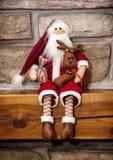 Weihnachtsmann machte vom Stoff sitzt mit Ren über dem ston Stockfotografie