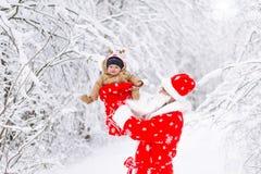 Weihnachtsmann mit Babykind in einem Winterwald lizenzfreies stockfoto