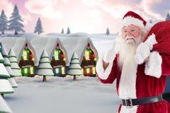 Weihnachtsmann mit dem Weihnachtsgeschenksack, der sich seine Daumen zeigt Stockfotografie