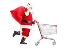 Weihnachtsmann mit einem Beutel, der einen Einkaufswagen drückt Stockbild