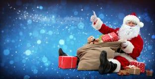 Weihnachtsmann mit einem Beutel voll von den Geschenken Stockfotos