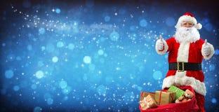 Weihnachtsmann mit einem Beutel voll von den Geschenken Stockbilder