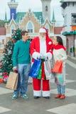 Weihnachtsmann mit einem jungen Paar Lizenzfreie Stockfotografie