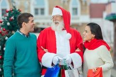 Weihnachtsmann mit einem jungen Paar Lizenzfreie Stockfotos