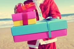 Weihnachtsmann mit Geschenken auf dem Strand Stockbilder