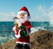 Weihnachtsmann mit Geschenken in einem Spray von Meer bewegt wellenartig Lizenzfreies Stockfoto