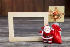 Weihnachtsmann mit roter Tasche und Geschenkbox und hölzerner Bilderrahmen Lizenzfreie Stockfotos