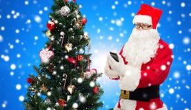 Weihnachtsmann mit Smartphone- und Weihnachtsbaum Stockfoto
