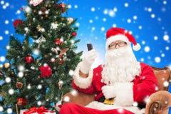 Weihnachtsmann mit Smartphone- und Weihnachtsbaum Stockfotografie