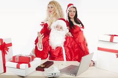 Weihnachtsmann mit zwei reizvollen Helfern in seinem Büro Stockfotografie
