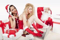 Weihnachtsmann mit zwei reizvollen Helfern in seinem Büro Stockbilder
