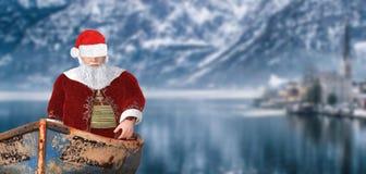 Weihnachtsmann-Segeln der frohen Weihnachten in einem Babyboot auf einem Gleichen in einer kalten Winterberglandschaft stockfotos