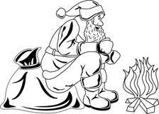 Weihnachtsmann sitzt durch das Feuer Lizenzfreie Stockfotos