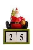 Weihnachtsmann-Statuette, die auf den Würfeln zeigen das Datum 25 lokalisiert auf weißem Hintergrund sitzt Lizenzfreies Stockbild