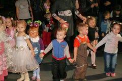 Weihnachtsmann trägt Geschenke Kinder an einem Kinderpartykostüm, der Karneval des neuen Jahres Stockbild