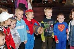 Weihnachtsmann trägt Geschenke Kinder an einem Kinderpartykostüm, der Karneval des neuen Jahres Lizenzfreie Stockbilder