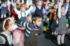 Weihnachtsmann trägt Geschenke Kinder an einem Kinderpartykostüm, der Karneval des neuen Jahres Lizenzfreies Stockfoto