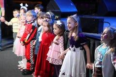 Weihnachtsmann trägt Geschenke Kinder an einem Kinderpartykostüm, der Karneval des neuen Jahres Stockfotografie