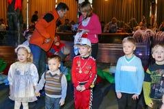 Weihnachtsmann trägt Geschenke Kinder an einem Kinderpartykostüm, der Karneval des neuen Jahres Stockfoto