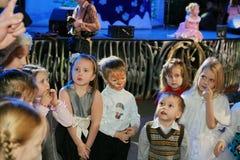 Weihnachtsmann trägt Geschenke Kinder an einem Kinderpartykostüm, der Karneval des neuen Jahres Stockbilder