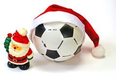 Weihnachtsmann und die Fußballkugel auf Weiß Stockfotos