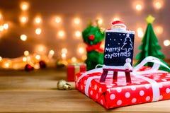 Weihnachtsmann und Geschenke und Spielwaren auf hölzernen Brettern und bokeh wärmen L Lizenzfreie Stockfotos