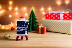 Weihnachtsmann und Geschenke und Spielwaren auf hölzernen Brettern und bokeh wärmen L Stockfotos