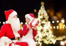 Weihnachtsmann und glückliches Mädchen mit Weihnachtsgeschenk lizenzfreie stockfotografie