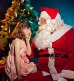 Weihnachtsmann und kleines Mädchen, die Geschenk anhalten stockbilder