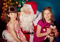 Weihnachtsmann und kleines Mädchen, die Geschenk anhalten lizenzfreie stockfotos