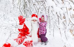 Weihnachtsmann und mit dem Baby, das im Schnee im Winterpark sitzt lizenzfreie stockfotografie