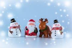 Weihnachtsmann und Ren stehen mit Gruppe des Schneemannes Stockbild