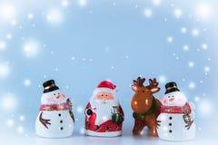 Weihnachtsmann und Ren stehen mit Gruppe des Schneemannes Stockfoto