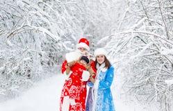 Weihnachtsmann und Schnee-Mädchen mit Baby scherzen im Winterwald stockfotos