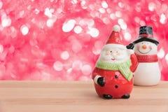 Weihnachtsmann und Schneemann auf dem Holztisch Stockfoto
