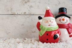 Weihnachtsmann und Schneemann auf dem Schnee Stockbilder