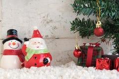 Weihnachtsmann und Schneemann auf dem Schnee mit Weihnachtsbaum Stockfotografie