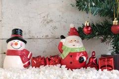 Weihnachtsmann und Schneemann auf dem Schnee mit Weihnachtsbaum Stockbilder