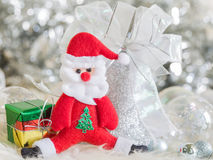 Weihnachtsmann und silberne Glocke, weißer silberner Bogen und Silberballdekoration auf Weihnachten Lizenzfreie Stockfotos