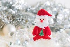 Weihnachtsmann und silberne Glocke, weißer silberner Bogen und Silberballdekoration auf Weihnachten Stockfoto