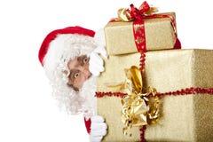 Weihnachtsmann versteckt sich hinter Weihnachtsgeschenkkästen Stockfoto
