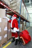Weihnachtsmann, welche nach Geschenken im Lagerhaus sucht Lizenzfreie Stockfotos