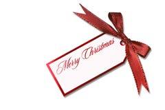 Weihnachtsmarke, die von einem gebundenen roten Feiertags-Bogen hängt Stockbilder