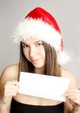 Weihnachtsmädchen, das ein unbelegtes Papier anhält Lizenzfreie Stockfotografie