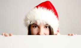 Weihnachtsmädchen, das hinter einem unbelegten Vorstand sich versteckt Stockfotografie