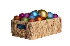 Weihnachtsmehrfarbige Bälle in einem Weidenkorb, lokalisiert auf einem weißen Hintergrund stockbild