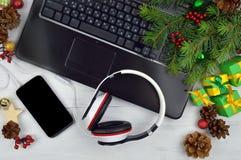 Weihnachtsmelodien Smartphone und Kopfhörer auf einem hölzernen backgro Lizenzfreie Stockbilder
