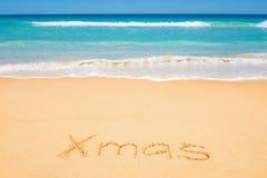 Weihnachtsmitteilung auf dem Strandsand Stockfoto