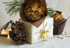 Weihnachtsnachtischkegel und Weihnachtsgeschenk auf einem hellen Hintergrund Lizenzfreie Stockfotos