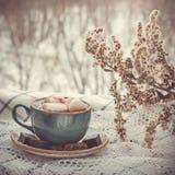 Weihnachtsniederlassung und -glocken Blauer Becher heißer Kaffee mit Eibisch auf weiße Servietten auf Fensterbrett lizenzfreies stockfoto